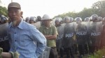 FILE - Villagers stand next to riot police deployed to Vietnam's northern Hung Yen province during a protest in April, 2012.